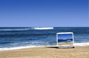 Ein Laptop auf einem Strand mit dem Meer dahinter. Der Laptop hat genau dieses Bild auch als Schreibtischhintergrund, so dass eine endlose Abfolge desselben Bildes im Bild im Bild im Bild entsteht.