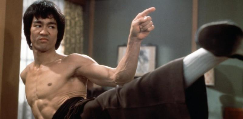 Bruce Lee, im Tritt, sehr cool, mit erhobenem Zeigefinger und verkniffenem Gesichtsausdruck