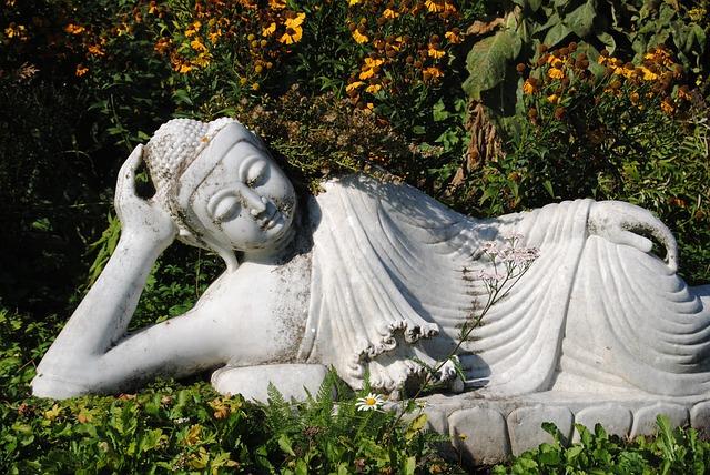 Eine Skulptur eines gemütlich zwischen Pflanzen auf der Seite liegenden Buddha.