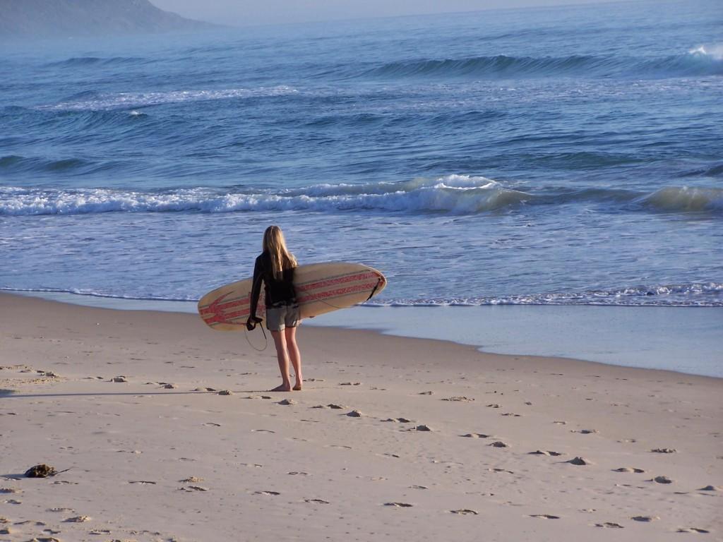 Eine junge Frau, die mit einem Surfbrett unter dem Arm am Strand langläuft.